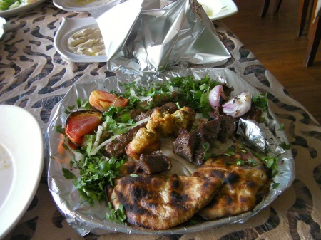 plate wrapped in aluminum foil containing mixed grilled meats
