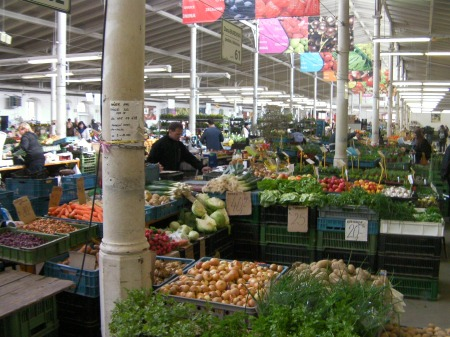 large warehouse room full of booths selling vegetables and fruit