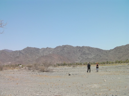 mountains in the distance, flat desert area in the foreground, two people walking