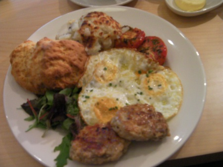plate of eggs, sausage patties, potatoes, and a biscuit