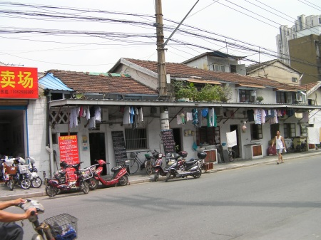building with scooters parked in front and laundry hanging from the awnings