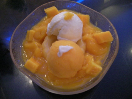 a bowl of mango pudding, chunks, and ice cream