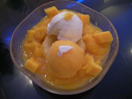 a bowl of mango pudding, chunks, and ice cream