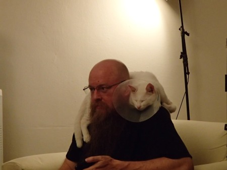 man with white cat laying on his shoulders