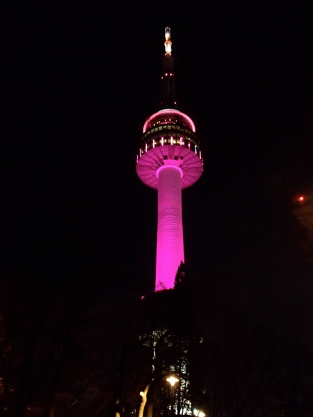 communications tower at night lit up pink