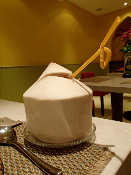 a coconut with a straw sticking out