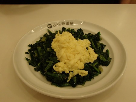 plate of cooked spinach topped with scrambled egg