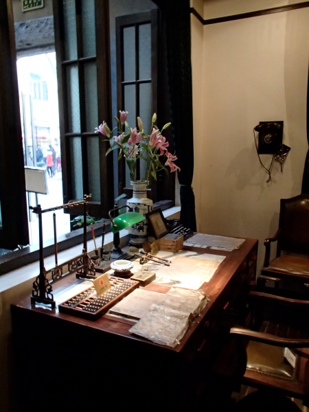 desk with abacus, papers, other items as museum display