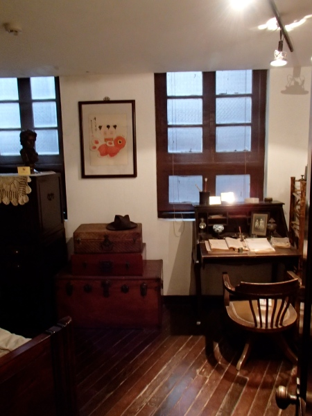 room with small desk and trunks