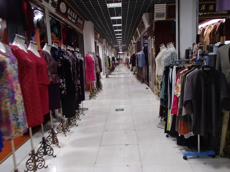 hallway lined with clothing shops but no customers