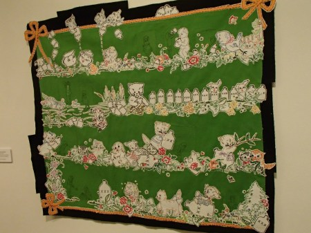 Hanging art quilt made with embroidery cut from tea towels and pillow cases