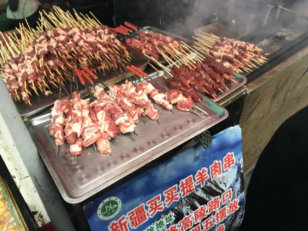 meat on skewers near a coal fired grill