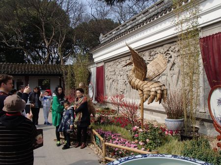 Garden entrance with people posing in front of bamboo crane sculptures