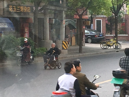 an elderly man in an electric wheelchair traveling down the street