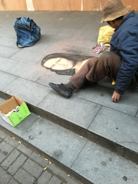 homeless man drawing the Mona Lisa in chalk on the sidewalk