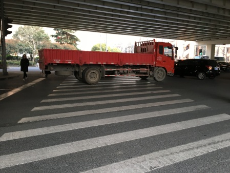 a large red truck blocking a very wide crosswalk