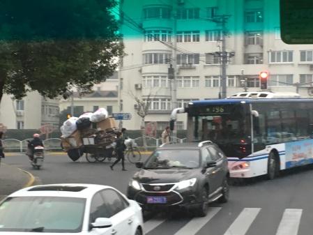 cars, bus, three wheeled cart, and chaos