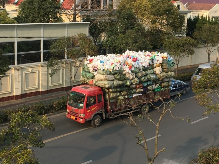 large truck filled with about two stories worth of plastic bottles