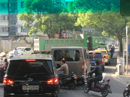 traffic blocked by a large green truck