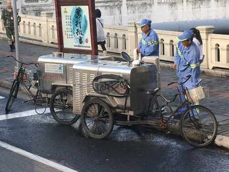 street washers filling up the tanks on their three wheeled bicycle street washing machines