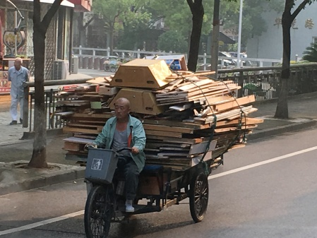 a three wheeled cart full of recycled wood