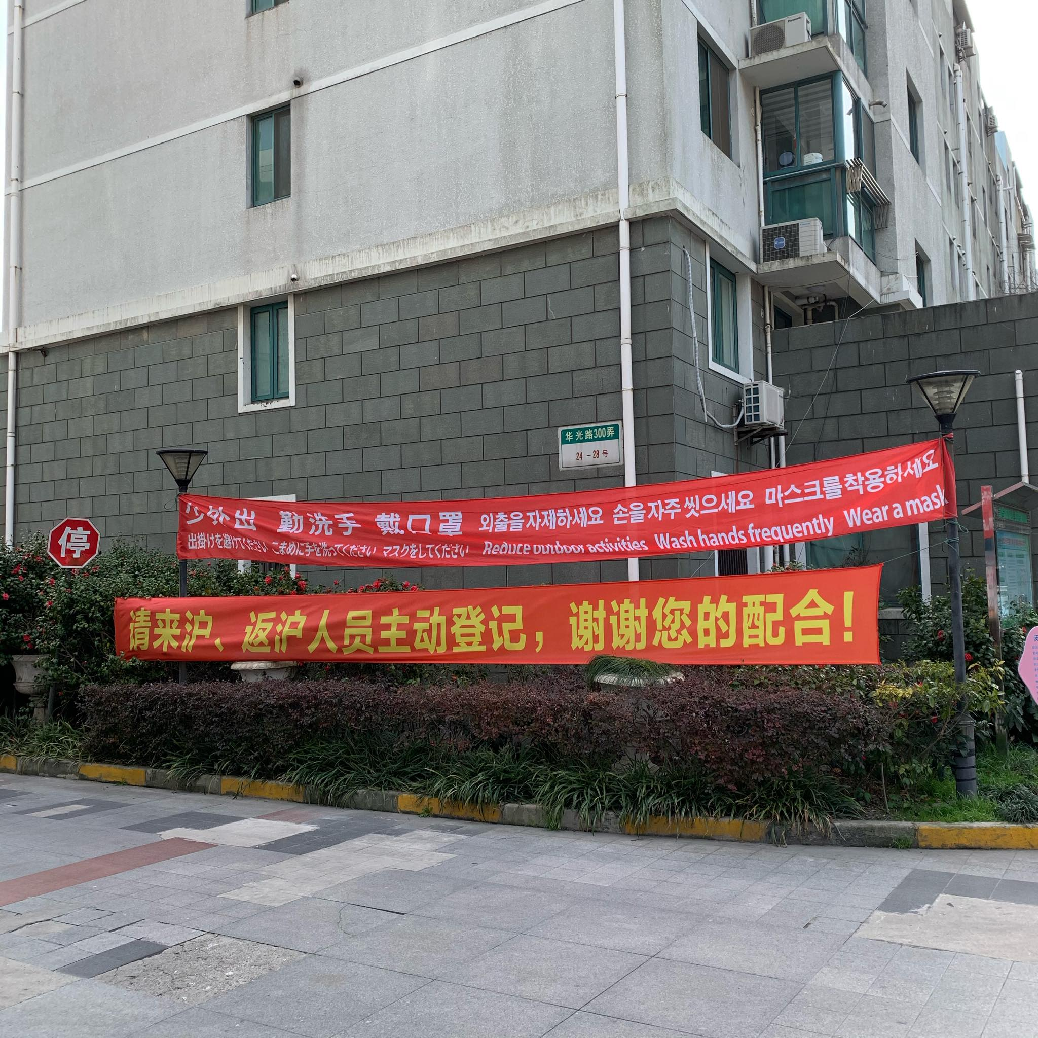 """red banners at apartment entrance stating """"reduce outdoor activities, wash hands frequently, wear a mask"""" in four languages"""