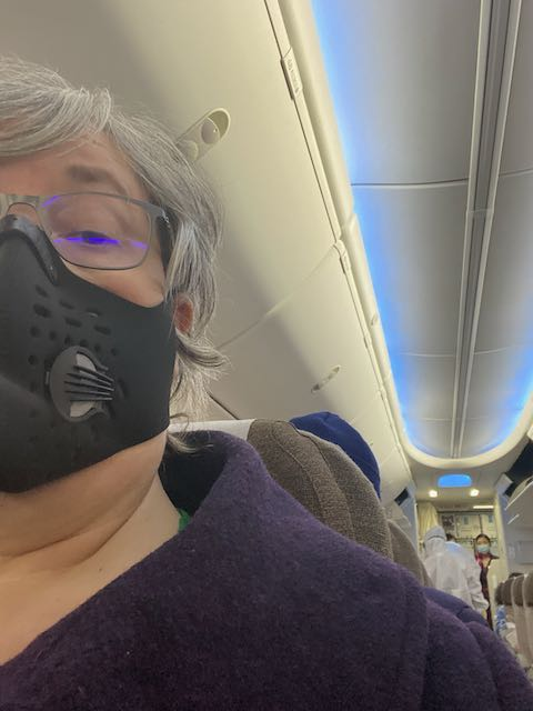 woman wearing black medical mask on a plane, at the back of the plane are medical inspectors wearing hazmat suits