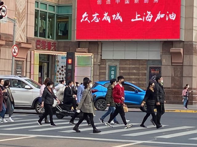 crosswalk where twelve people are crossing all wearing face masks