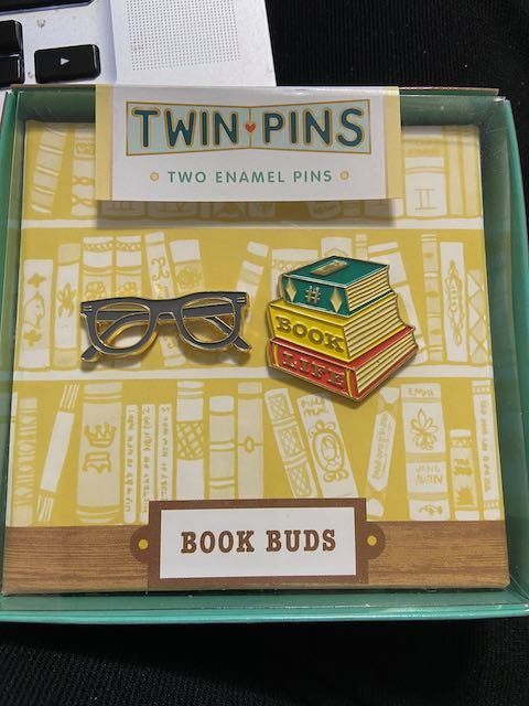 a box containing two pins, one shaped like eyeglasses, the second shaped like a pile of three books
