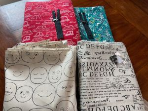four fabrics including smiley faces, garbled text, cars, and unicorn prints