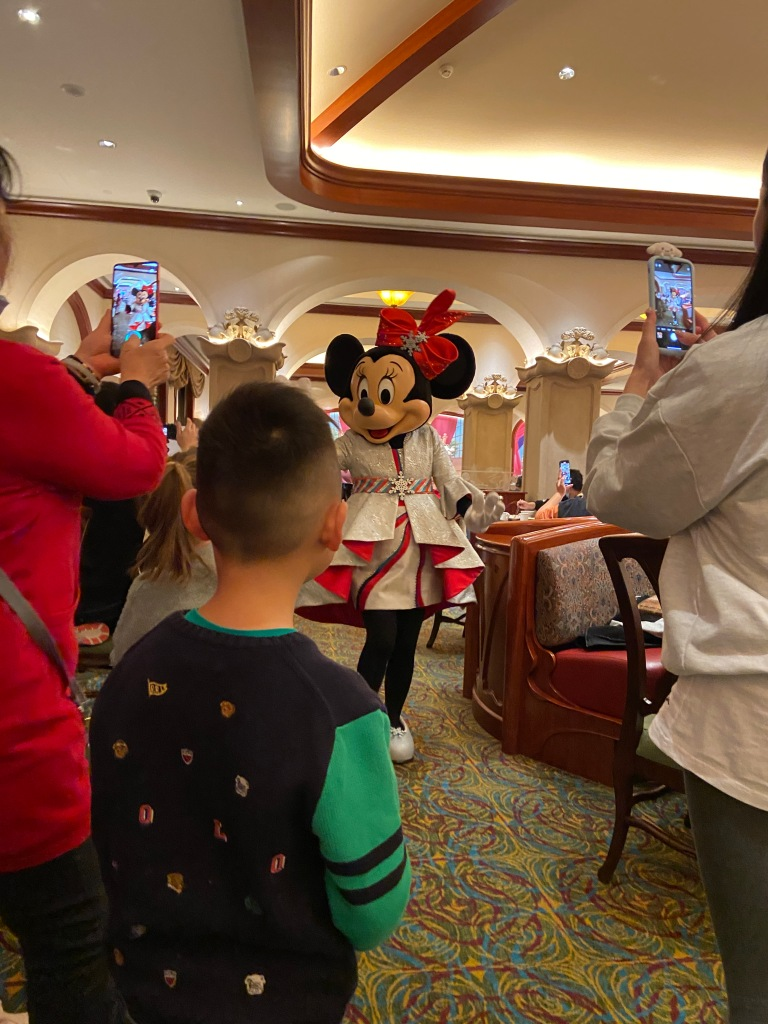 Minnie Mouse being photographed by people in the buffet restaurant