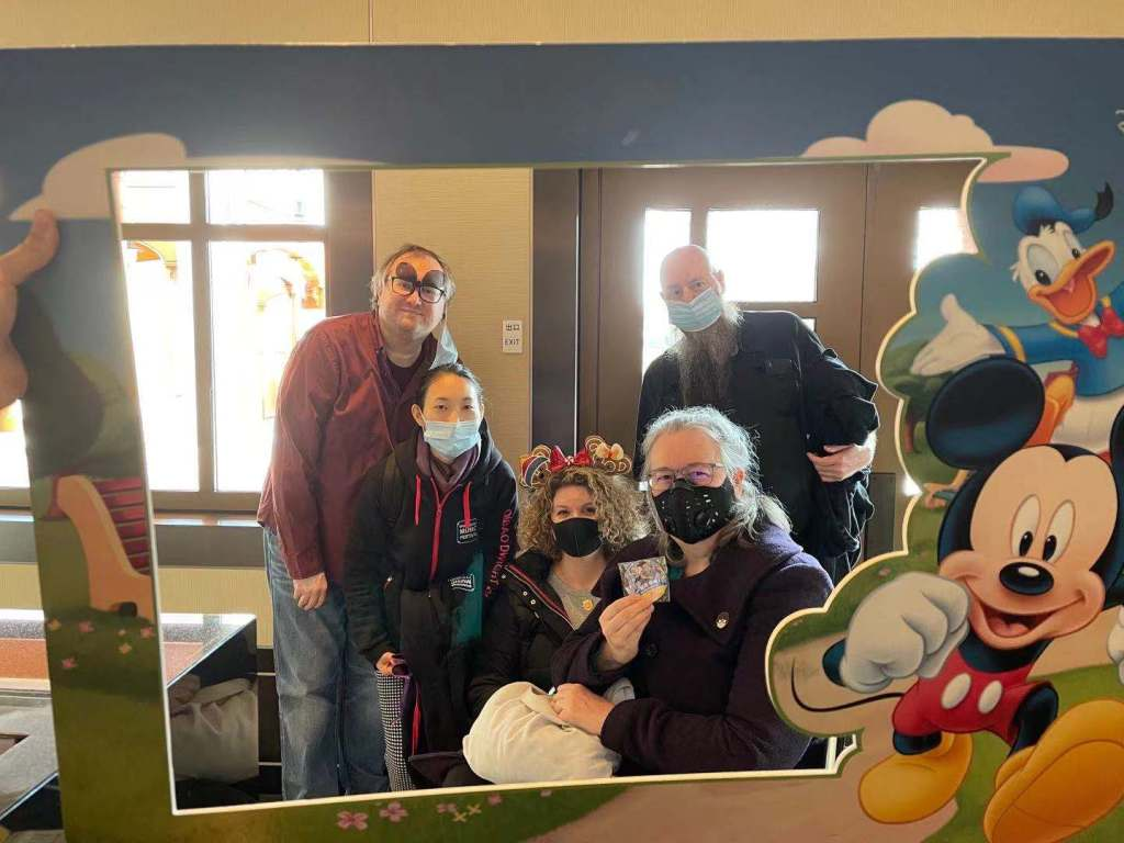 five friends all wearing medical face masks framed by a Disney themed frame
